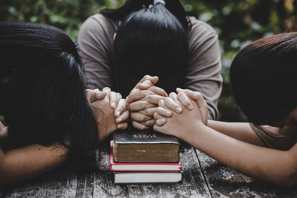 Three women praying for each other.